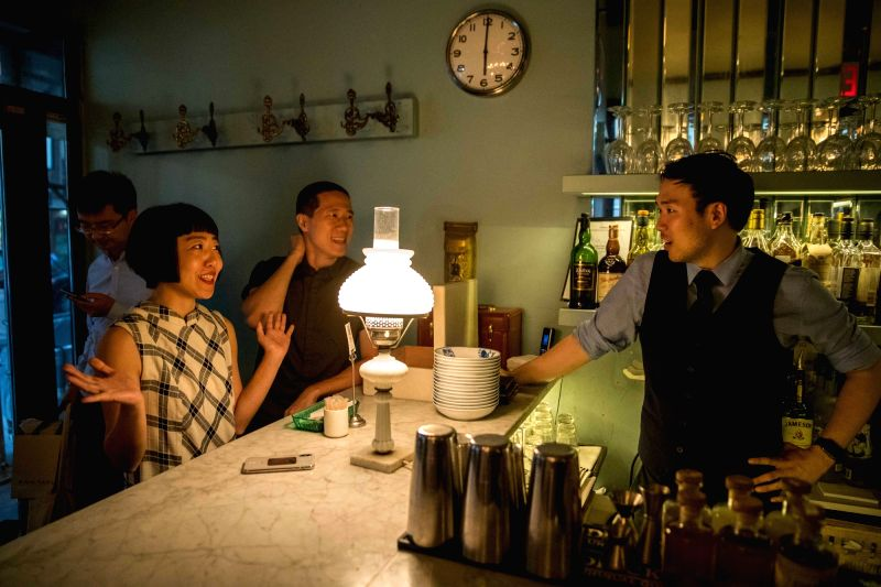 NEW YORK, July 17, 2018 - Restaurant owner Wang Yiming (3rd R) and Zhang Xian (2nd R) talk with a bartender at Cafe China in New York, the United States, on June 27, 2018.Walking in the bustling ...