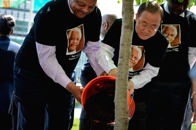 United Nations Secretary-General Ban Ki-moon (R) adds soil for a tree during a ceremony commemorating Nelson Mandela International Day, in front of the UN ...