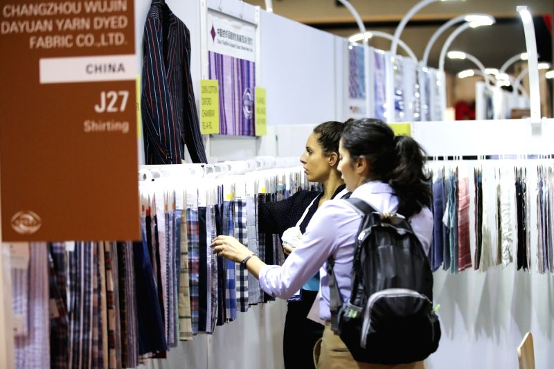 NEW YORK, July 24, 2018 - Buyers look at exhibits of a Chinese fabric producer at the Chinese Textile and Apparel Trade Show in New York, the United States, July 23, 2018. The 19th China Textile and ...