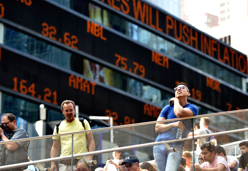 Tourists gather in front of the screens which shows the Dow Jones Industrial Index at the New York's Time Square in New York, the United States on July 3, 2014. ...