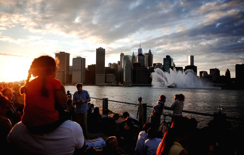 People assemble at the Brooklyn Bridge Park waiting for the fireworks display to commemorate the Independence Day in New York, the United States on July 4. The ...