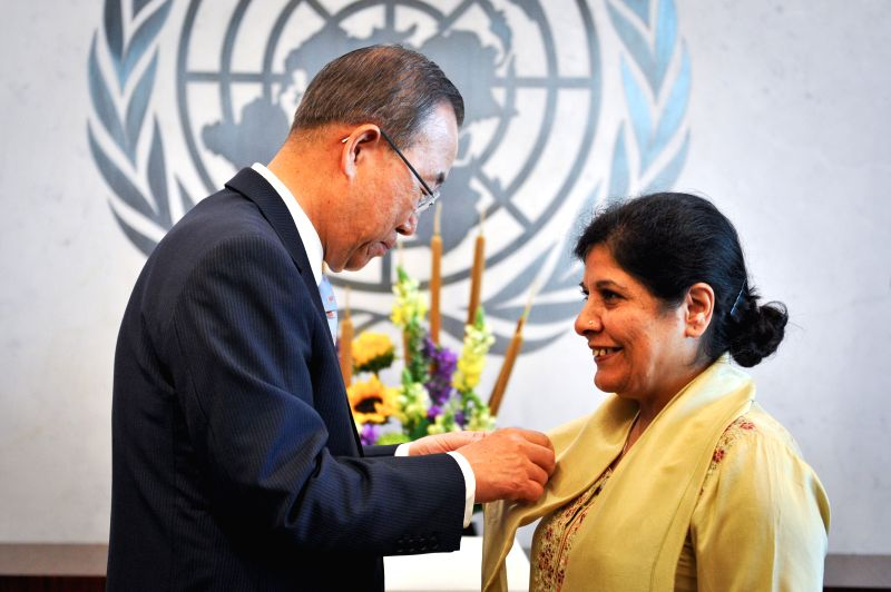 Shamshad Akhtar (R), Executive Secretary of the UN Economic and Social Commission for Asia and the Pacific, has a pin attached by UN Secretary-General Ban Ki-moon, .