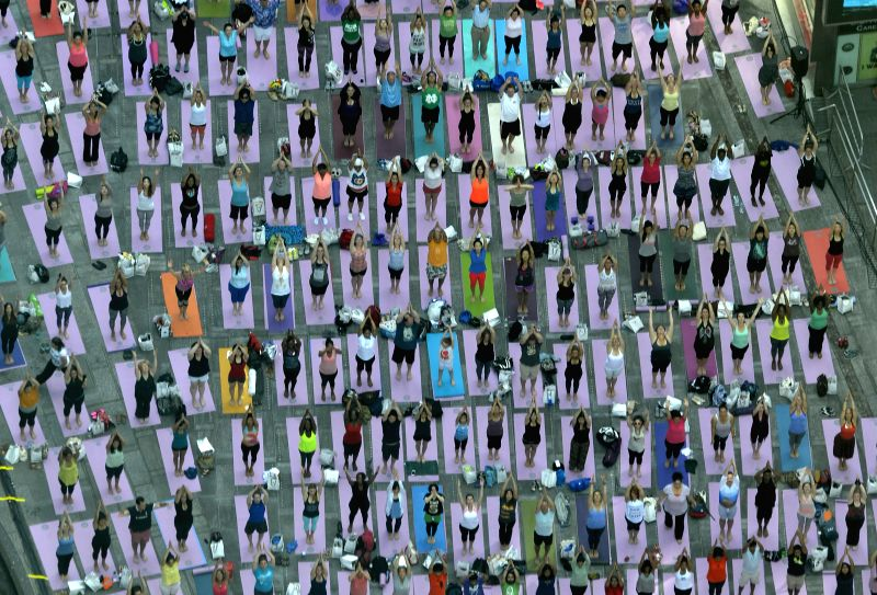 "Enthusiasts practice yoga during the ""Solstice in Times Square"" event at Times Square in New York, the United States, June 21, 2014. Hundreds of New ..."