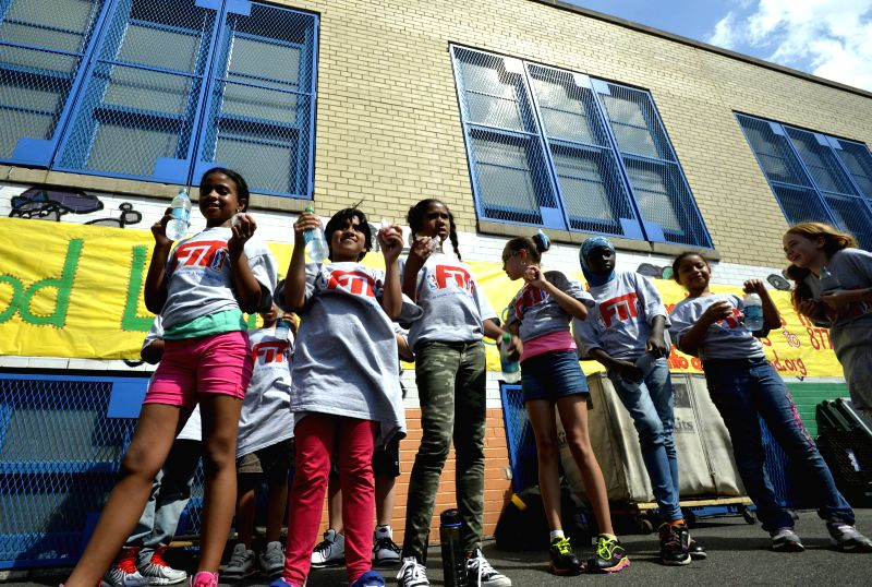 Children enjoy free drinks offered by free summer meals plan in New York, the United States, on June 25, 2014. New York City officials have announced free summer ..