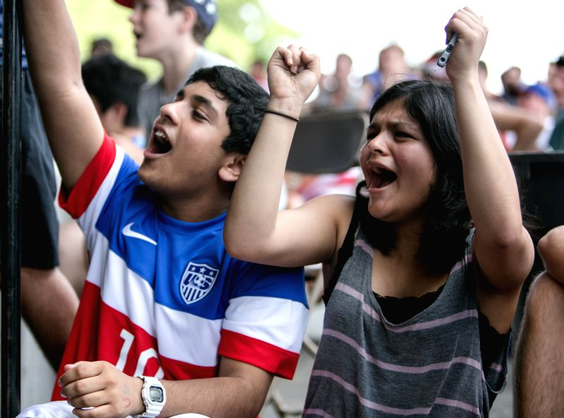 Fans of the U.S. cheer for their team while watching the broadcast of a Group G match between the U.S. and Germany of 2014 FIFA World Cup on Governors Island in ...