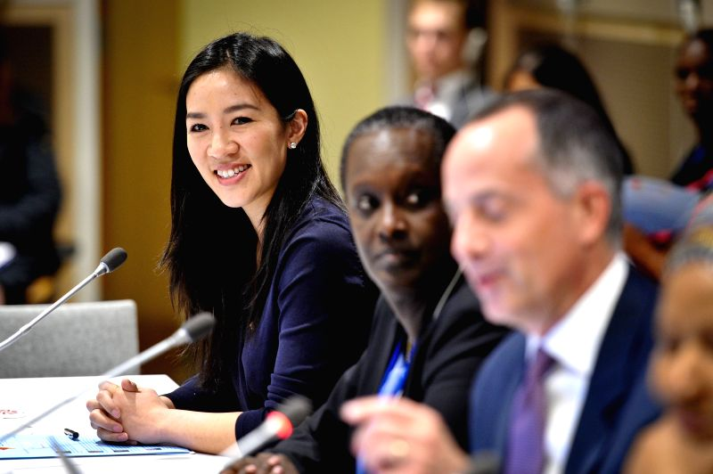 """Olympic figure skater Michelle Kwan (1st L) smiles during an event titled """"the Place of Sport for Women's Empowerment Post-2015"""", at the UN headquarters ..."""