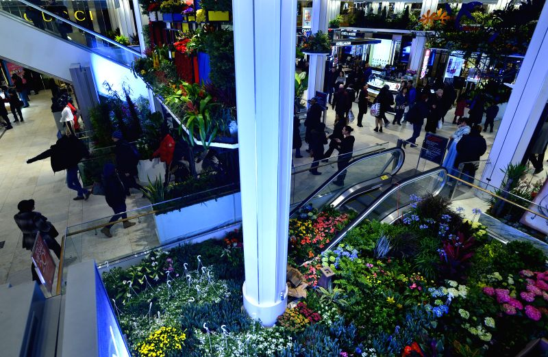 People pass by floral decorations inside the Macy's department store in New York, the United States, March 20, 2015. Macy's Herald Square unveiled its latest work ...