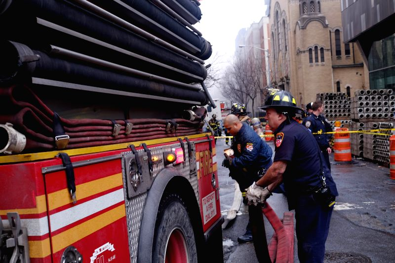 Firefighters prepare to work at the site where a fire broke out in New York, the United States, on March 26, 2015. A massive fire broke out after an explosion at ...
