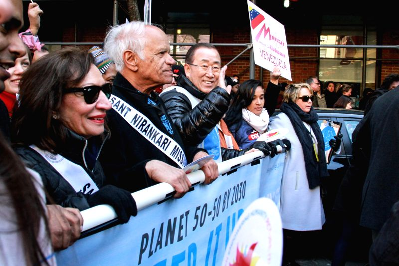 United Nations Secretary-General Ban Ki-moon (C) waves as he participates in the International Women's Day March for Gender Equality and Women's Rights, in New ...