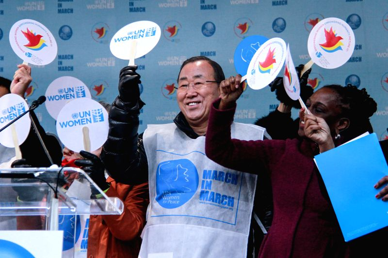 United Nations Secretary-General Ban Ki-moon (C) waves prior to the start of the International Women's Day March for Gender Equality and Women's Rights, in New ...