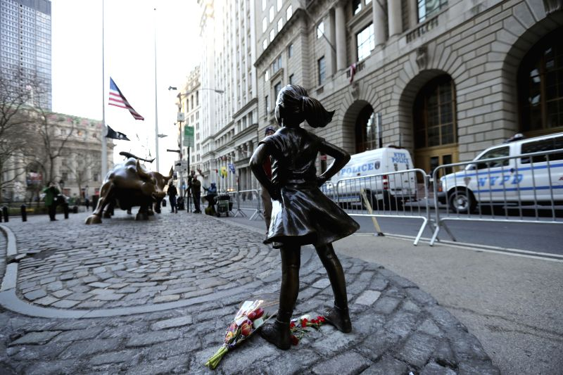 """NEW YORK, March 9, 2017 - Photo taken on March 9, 2017 shows the """"fearless girl"""" statue facing the bronze bull statue near the Wall Street in New York, the United States. The """"fearless ..."""