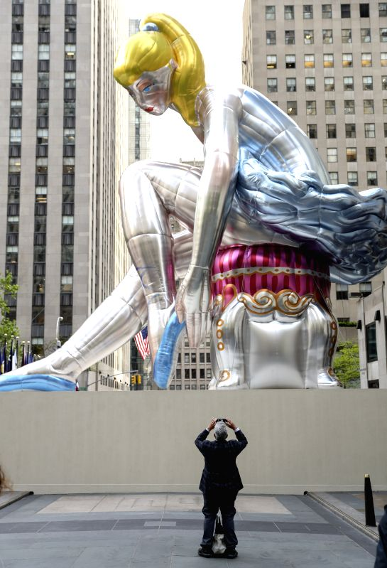 NEW YORK, May 12, 2017 - A man takes photos of the Seated Ballerina at Rockefeller Center in New York, the United States, on May 12, 2017. Seated Ballerina, the public art exhibition of a 45-foot ... - Jeff Koons