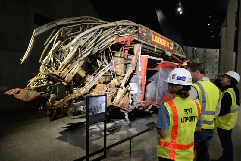 Staff members view a destroyed fire truck during a preview of the National September 11 Memorial Museum in New York, May 14, 2014. The National September 11 ...