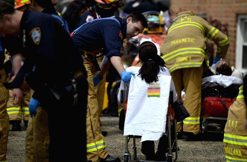 An injured person is treated in the New York City borough of Queens, May 2, 2014. An F train carrying some 1,000 passengers and heading towards Manhattan ran off the