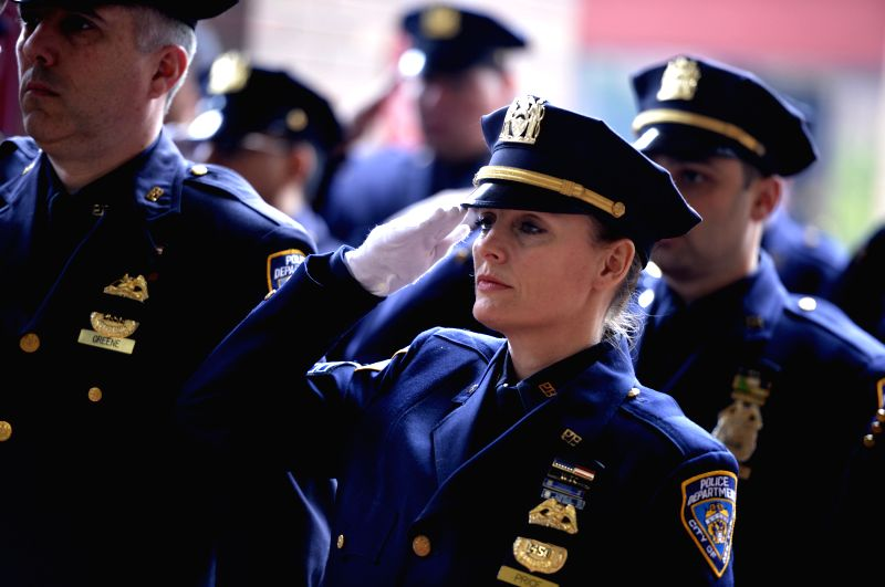 Police officers salute at a memorial ceremony to honor 13 fallen members of the New York City Police Department during 2013, at One Police Plaza in New York, the ...