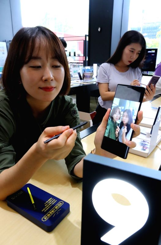 New York: People experience Samsung Electronics Co.'s Galaxy Note 9 phablet at a KT outlet in Seoul on Aug. 10, 2018. The company held a showcase event in New York the previous day for the new ...