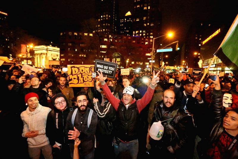 New York: People stage a demonstration in New York after the announcement that police officer Darren Wilson would not be indicted for shooting to death unarmed 18-year-old Michael Brown, on Nov 26, ..
