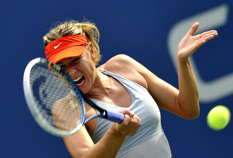 Maria Sharapova of Russia returns a shot during the women's singles fourth round match against Caroline Wozniacki of Denmark at the 2014 U.S. Open in New York, the
