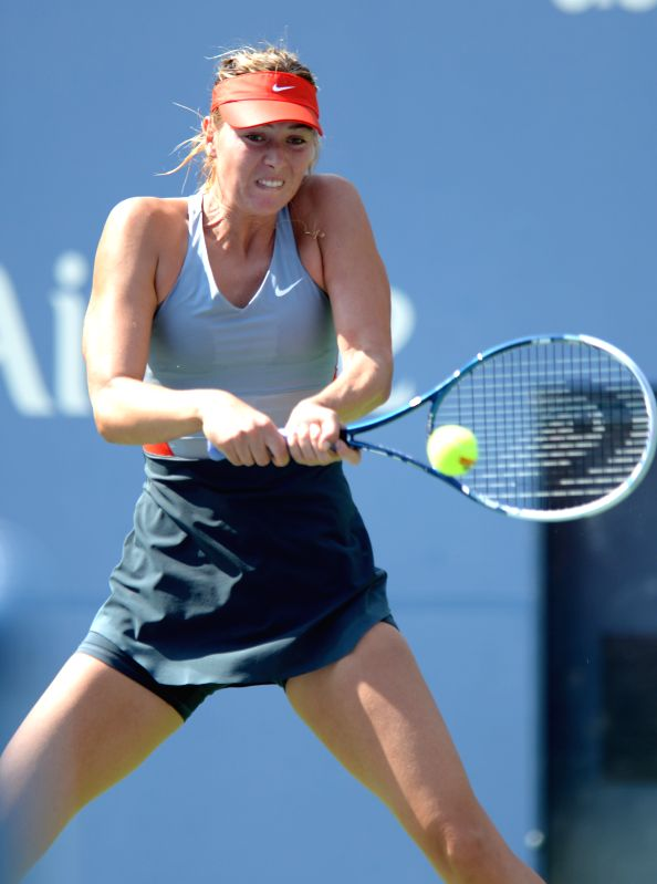 Maria Sharapova of Russia returns a shot against Caroline Wozniacki of Denmark during the fourth round match of women's singles at the 2014 U.S. Open in New York, .