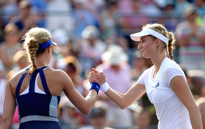 Ekaterina Makarova (R) of Russia and Eugenie Bouchard of Canada shake hands after their women's singles fourth round match at the 2014 U.S. Open in New York, the ..