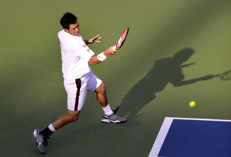 Kei Nishikori of Japan returns a shot to Stan Wawrinka of Switzerland during the Men's Singles Quarterfinals match at the 2014 U.S. Open in New York, the United ...