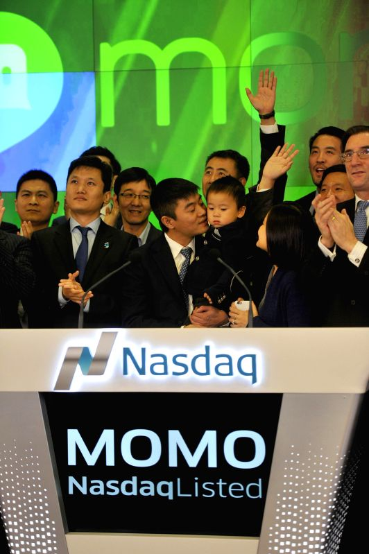 New York (U.S.):  Yan Tang (C, front), founder and chief executive officer of China's mobile social networking platform Momo Inc. attends the ceremony of ringing the opening bell at the NASDAQ in New