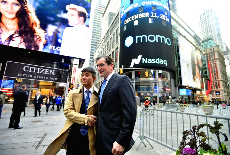 New York (U.S.): Yan Tang (L), founder and chief executive officer of China's mobile social networking platform Momo Inc.poses for a photo with Robert Greifeld, chief executive officer of the Nasdaq .