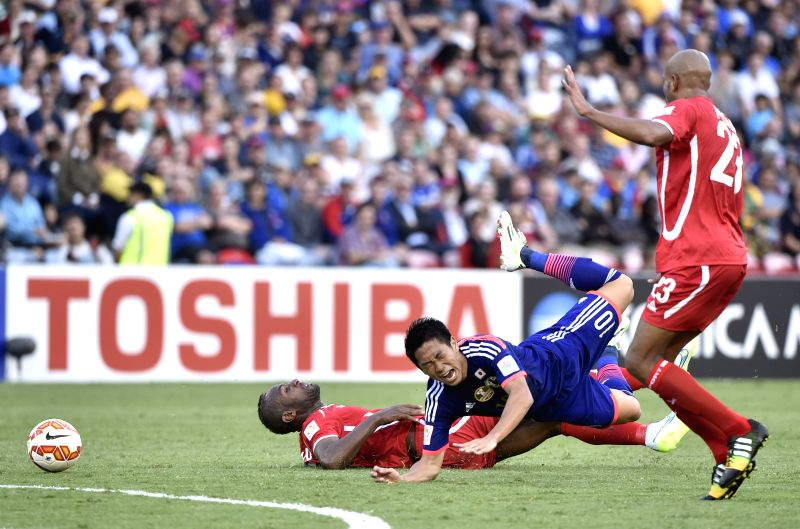 Shinji Kagawa (C) of Japan falls over during a Group D match against Palestine at the AFC Asian Cup in Newcastle, Australia, Jan. 10, 2015. Japan won 4-0. ...