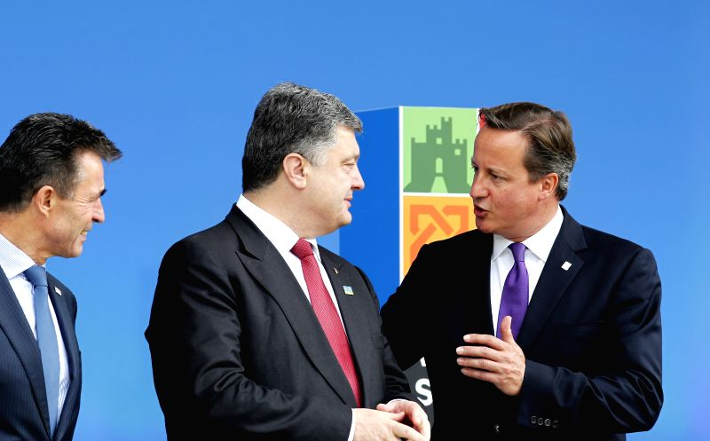 The NATO Secretary General Anders Fogh Rasmussen (L), Ukrainian President Petro Poroshenko (C) and British Prime Minister David Cameron interact at the NATO Summit . - David Cameron
