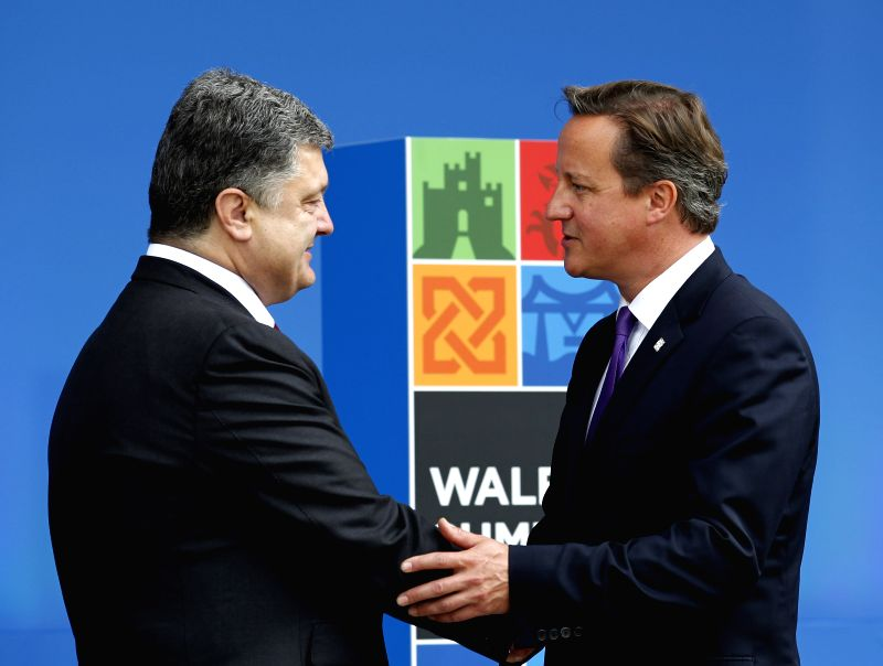 Ukrainian President Petro Poroshenko (L) shakes hands with British Prime Minister David Cameron at the NATO Summit 2014 in Newport, Wales, the United Kingdom, Sept. - David Cameron
