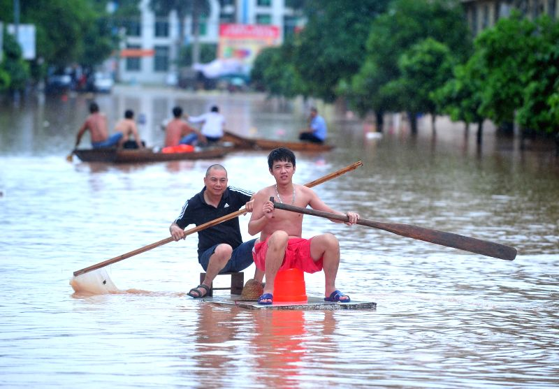 Local residents row out on a flooded road after landfall of the typhoon Rammasun in Ningming County, south China's Guangxi Zhuang Autonomous Region, July 21, 2014.