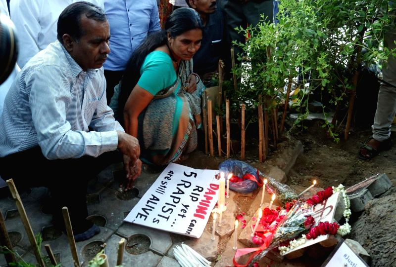 "Nirbhaya's parents participate in a candlelight vigil after calling it a ""rarest of rare"" case, the Supreme Court upheld the death sentence on all four convicts in the brutal ..."
