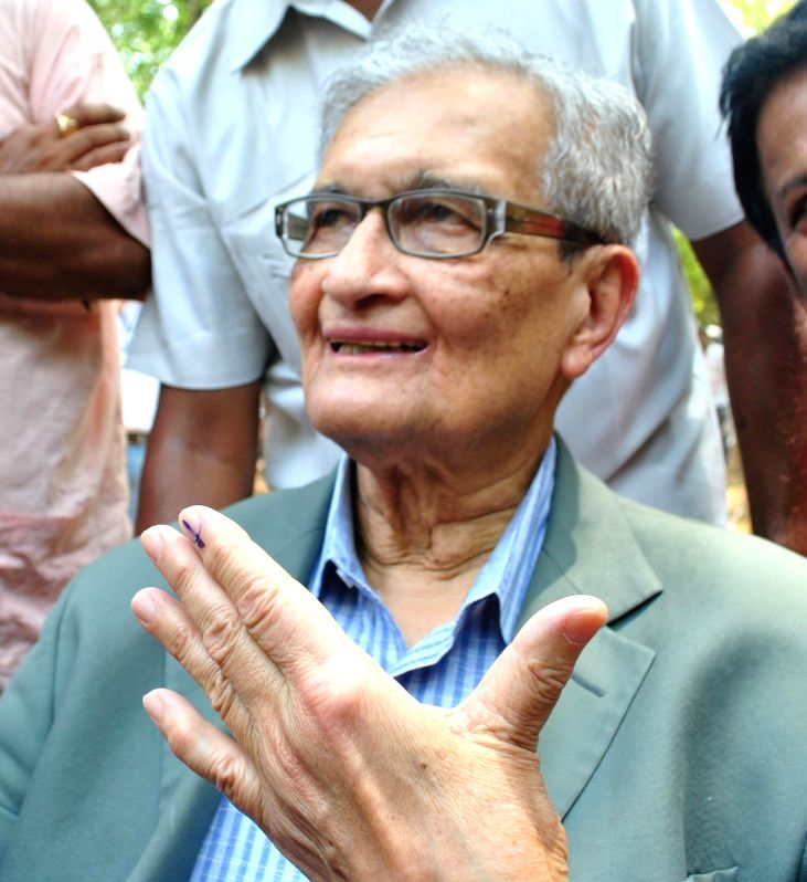 Nobel laureate Amartya Sen shows his fore finger marked with phosphorous ink after casting his vote at a polling booth during the seventh phase of 2014 Lok Sabha Polls in Bolpur of West Bengal's ...