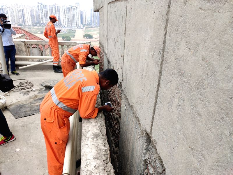 Noida: Operations being carried out to retrieve the body of a woman lying between two high-rise buildings near Amrapali Silicon City Society after residents complained about foul smell, in Noida on July 2, 2019.