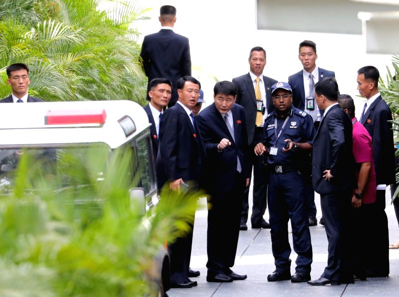 North Korean guards talk with a local policeman near the St. Regis Hotel in Singapore on June 10, 2018. The hotel is believed to be the lodging for North Korean leader Kim Jong-un during ...