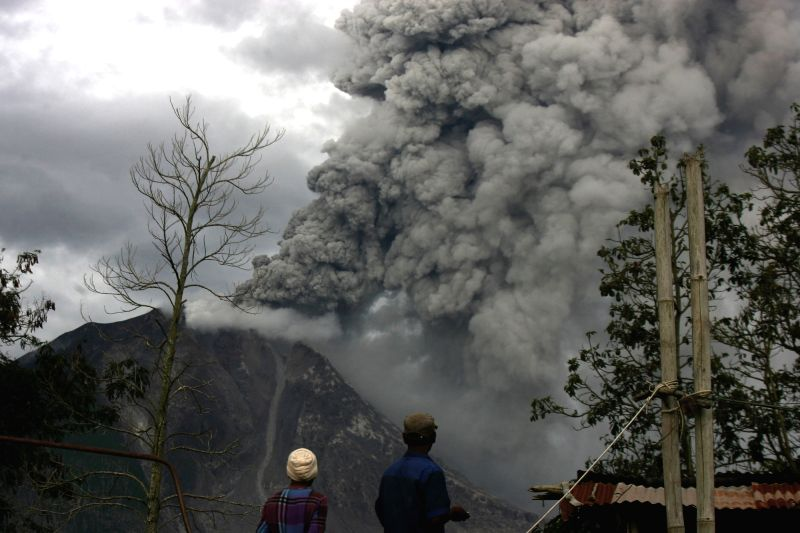 NORTH SUMATERA, May 24, 2017 - People watch Mount Sinabung spewing out volcanic ash, in Tiga Pncur village, Karo, North Sumatera, Indonesia, on May 24, 2017. Mount Sinabung is one of Indonesia's 129 ...
