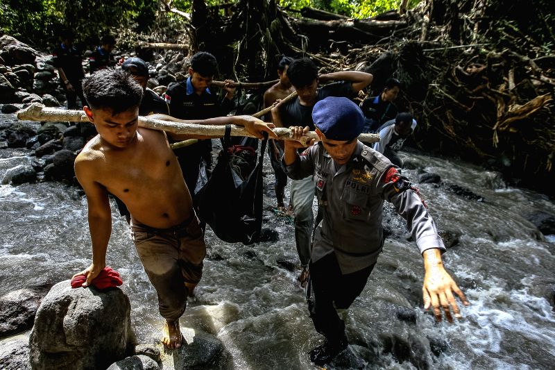 NORTH SUMATRA, May 16, 2016 - Members of search and rescue teams carry plastic bags containing bodies of victims in flash floods at Deli Serdang in North Sumatra, Indonesia, May 16, 2016. Flash ...