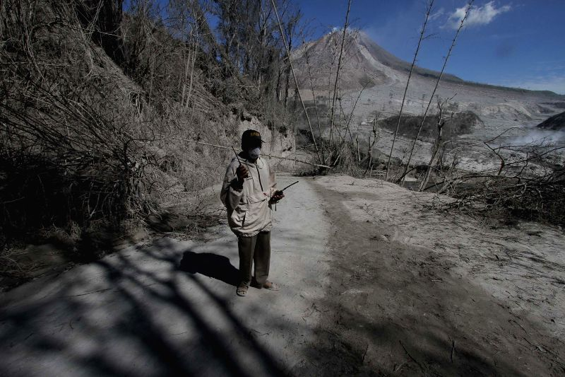 NORTH SUMATRA, May 24, 2016 - A man using walkie-talkie inspects an empty village hit by Mount Sinabung's eruption, in Gamber village, North Sumatra, Indonesia, May 23, 2016. At least six people were ...