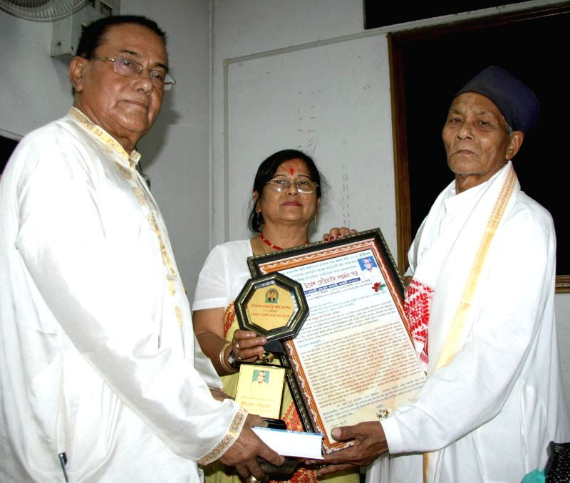 Noted journalist Umesh Chetia receives Golok Raimedhi Smarok Karmajogi Bota during a programme organised by Golok Raimedhi Smriti Prakashon in Guwahati on April 10, 2014.