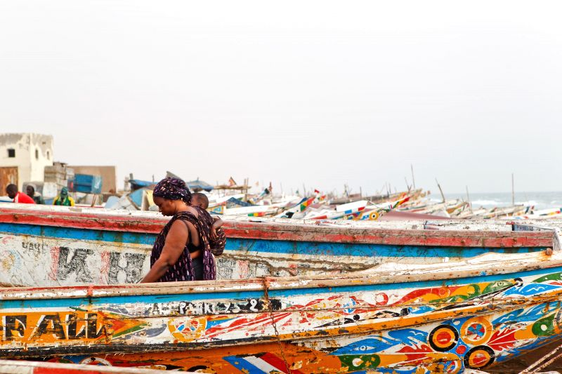 A woman walks through the boats at a fish market in Nouakchott, capital of Mauritania, June 22, 2014.