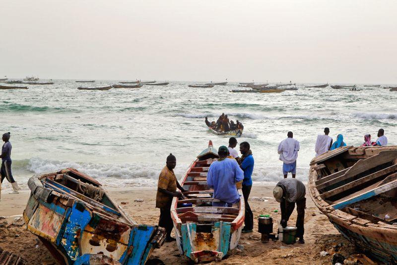 Fishermen watch the boats approaching the shore at a fish market in Nouakchott, capital of Mauritania, June 22, 2014.
