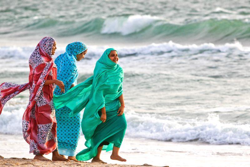 Muslims take a walk on the beach in Nouakchott, capital of Mauritania, June 21, 2014.