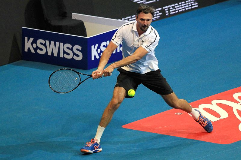 Obi UAE Royals' player Goran Ivanisevic of Croatia returns the ball against OUE Singapore Slammers' player Carlos Moya of Spain during their match in the ...