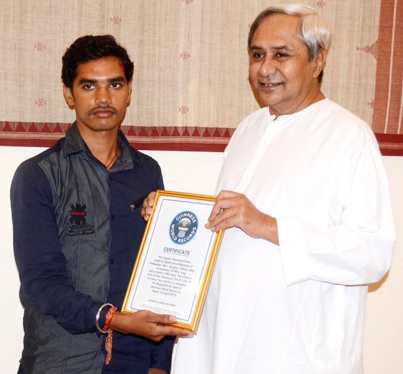 Odisha Chief Minister Naveen Patnaik with Balakrushna Maharana, whose name was registered in the Guinness Book of World Records for making the longest thermocol  chain measuring 70 metres, at the ... - Naveen Patnaik