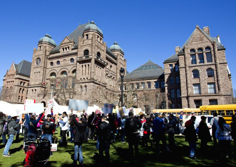 Protesters hold banners during a rally against the Ontario's new sex education curriculum in front of the Ontario Legislature in Toronto, Canada, April 14, 2015. ...