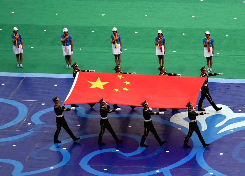 Flag-bearers carry the national flag of China into the stadium for the opening ceremony of the 10th National Traditional Games of Ethnic Minorities of China in Ordos, ...