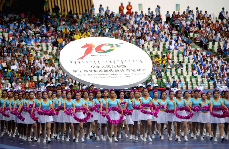 The emblem of the event is carried into the stadium during the opening ceremony of the 10th National Traditional Games of Ethnic Minorities of China in Ordos, north ...