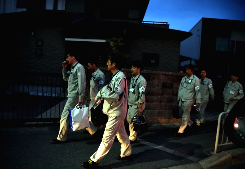 OSAKA, June 18, 2018 - Engineers walk at a street in Takatsuki, Osaka, Japan, on June 18, 2018. At least three people have been confirmed dead and more than 90 others injured as a result of a 6.1 ...