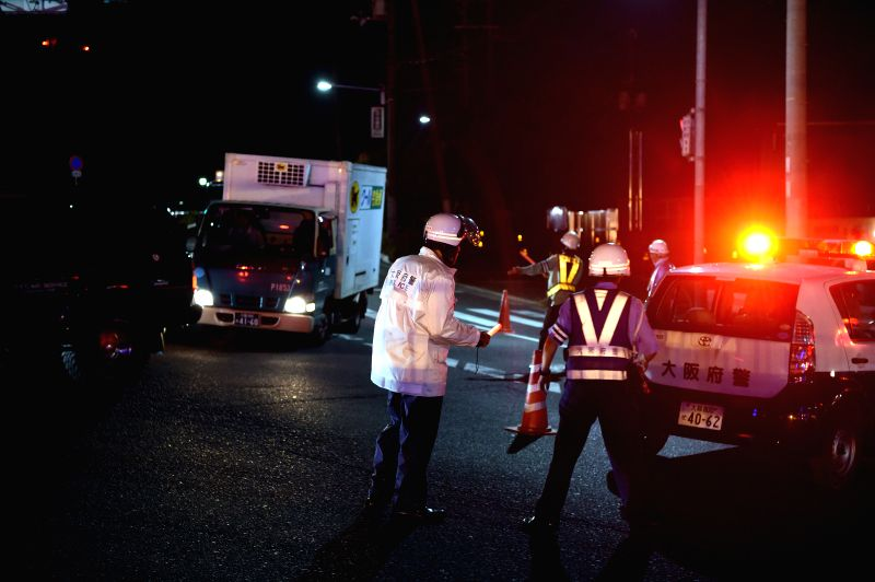 OSAKA, June 18, 2018 - Policemen lead vehicles away at a site of a damaged road in Osaka, Japan, on June 18, 2018. At least three people have been confirmed dead and more than 90 others injured as a ...