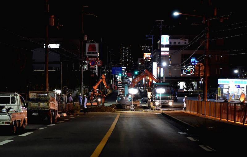 OSAKA, June 18, 2018 - Workers work at a site of a damaged road in Osaka, Japan, on June 18, 2018. At least three people have been confirmed dead and more than 90 others injured as a result of a 6.1 ...